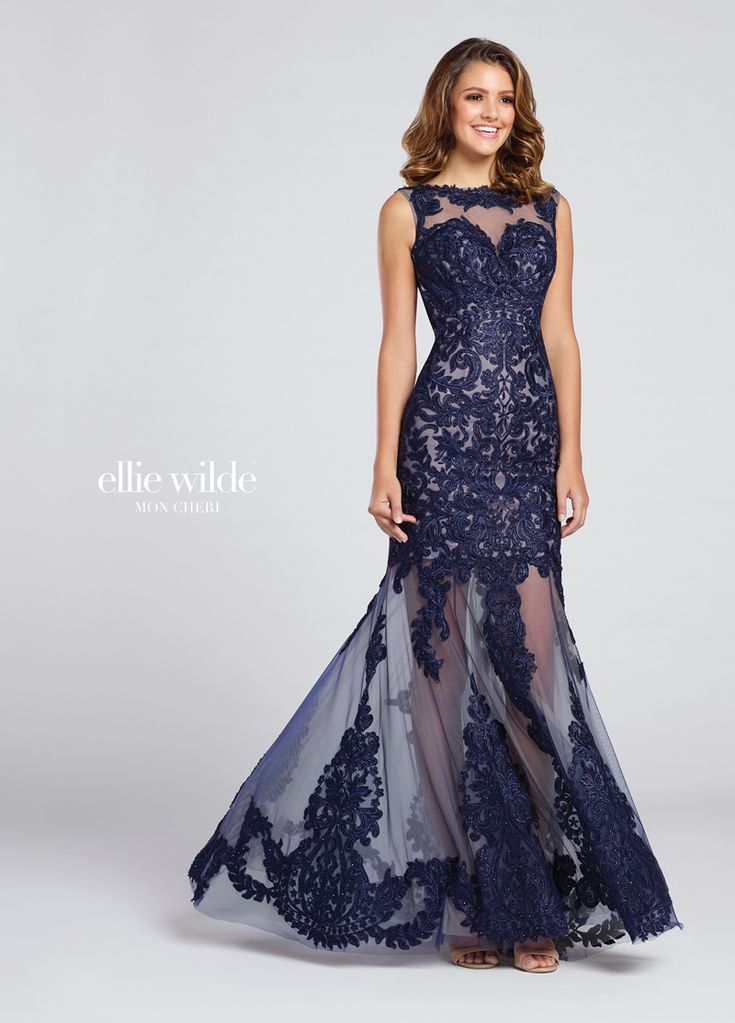 The Ellie Wilde EW117084 #prom dress features a lace-appliqued #tulle overlay, styled with a #bateau neckline, low #scoop back and semi-sheer lower skirt. The #cocktail-length sweetheart lining stands out beneath the illusion yoke. Heat-set stones are scattered all over this sleeveless fit and flare dress, which glides with a court train. Available in sizes 0 to 16.