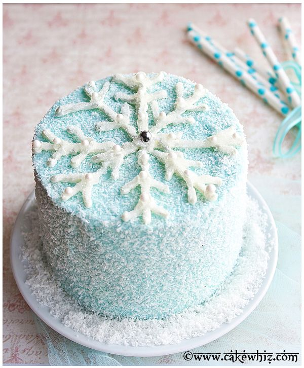 round blue iced cake covered in shredded coconut and a white chocolate snowflake with silver balls and edible glitter