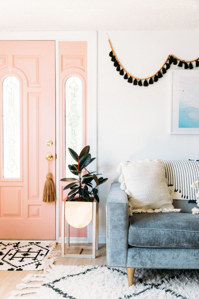 Pink door inside. Bohemian decoration, light gray blue couch
