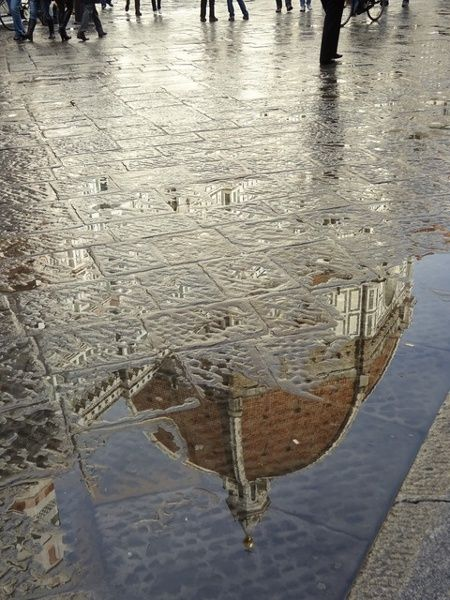 Rain glistening on the pavement in Florence The Duomo reflected in the puddles. Florence in November