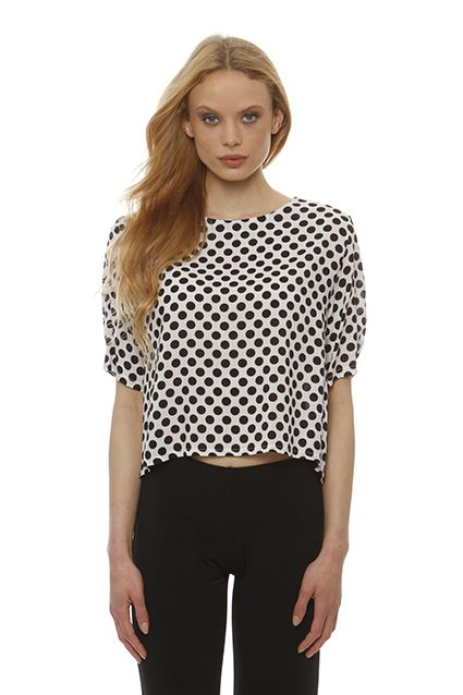 Asymmetrical black and white polka dot blouse with short sleeves, round neck .The red buttons at  the back side give elegance to your daily appearances