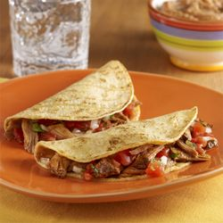 Carnitas Tacos: A Mexican-style pork taco recipe flavored with orange juice and spices, then topped with pico de gallo