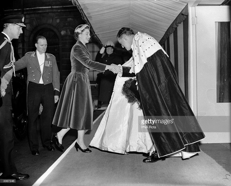 Queen Elizabeth II is greeted by the Lord Mayor of London, Cuthbert Ackroyd, upon her arrival at a luncheon held at London's Guildhall, February 22, 1956.