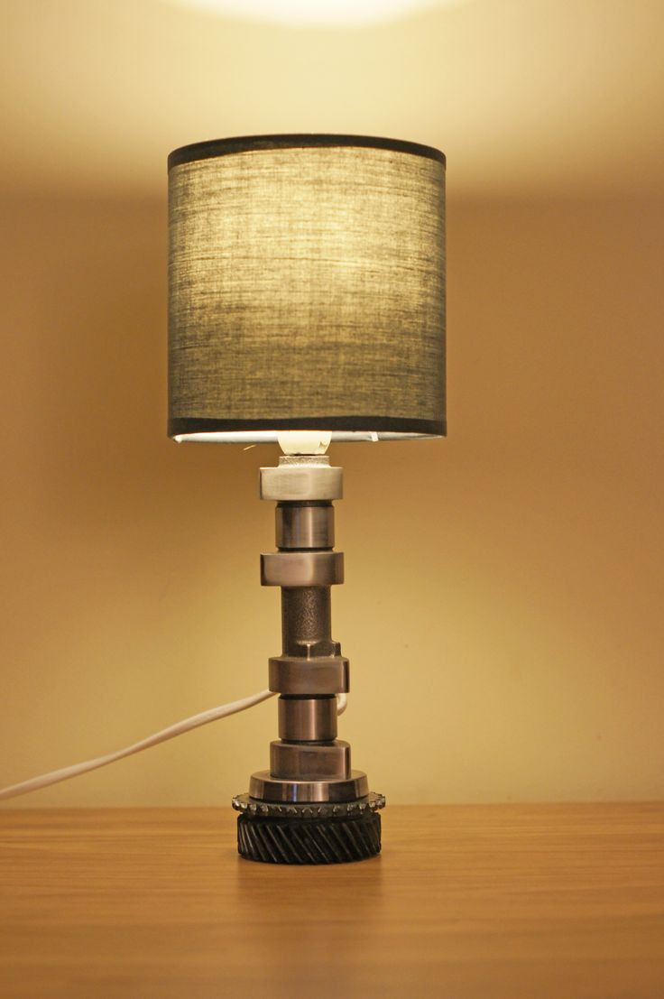 Nocna lampka wykonana z części wałka rozrządu oraz trybu ze skrzyni biegów jako podstawy. Całość polakierowana bezbarwnym lakierem. Dane techniczne: - wysokość 31,5 cm,  - średnica klosza 12,5 cm, -  waga 1,4 kg,  - długość kabla 105 cm, - gwint żarówki E14, - moc max 40W.