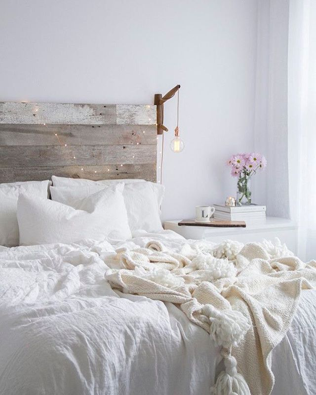 Rustic headboard with fairy lights in the bedroom of @lindsaymarcella