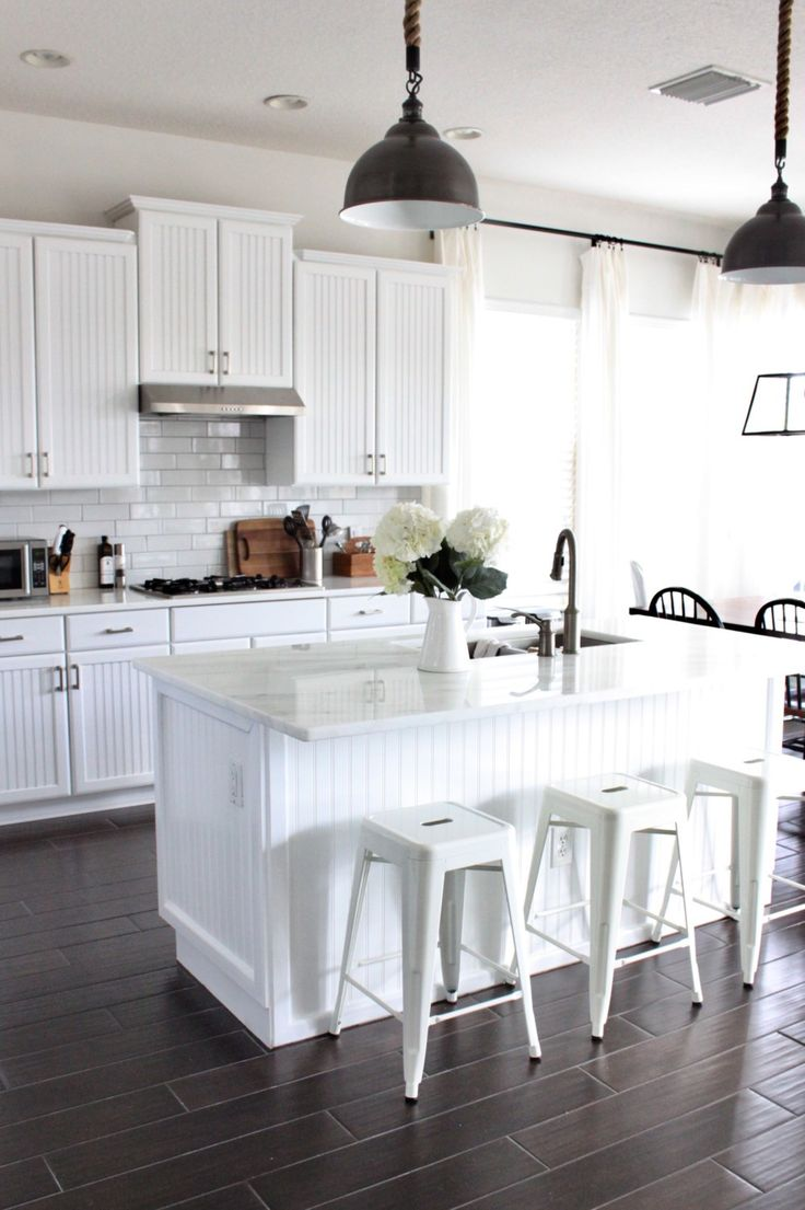 """Yesterday, I shared some photos of our Family Room with the new flooring and wall color, and I am back today with """"after"""" photos from our kitchen reno! If you remember, we had a beige ceramic tile flooring, a split bar height/counter height island with drywall front, and black Corian countertops. The bead board cabinets …"""