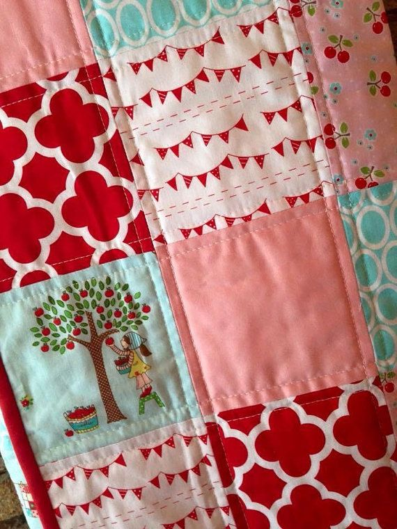 We just love this combination of Red, Aqua and Pink! This quilt features adorable prints with little boys and girls doing fun everyday things. Complimented with flags and cherries, this quilt is too cute to pass on! A modern quilt ready to brighten up a special baby girls nursery! The backing is white with a little bit of patchwork adding a fun detail to the back. Finished off with bold red binding to frame it, which is hand stitched. Finished size approx. 35 x 44 (90 x 112 cm) Looking for…