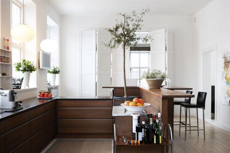 Köket i valnöt, rostfritt och granit är beställt från Kvänum. what ever that says, love the tree in the kitchen.