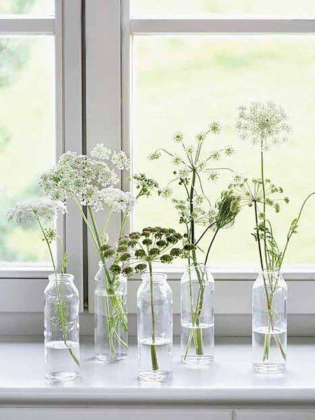 Decoración de verano con flores sencillas de la calle y mini jarrones transparentes.