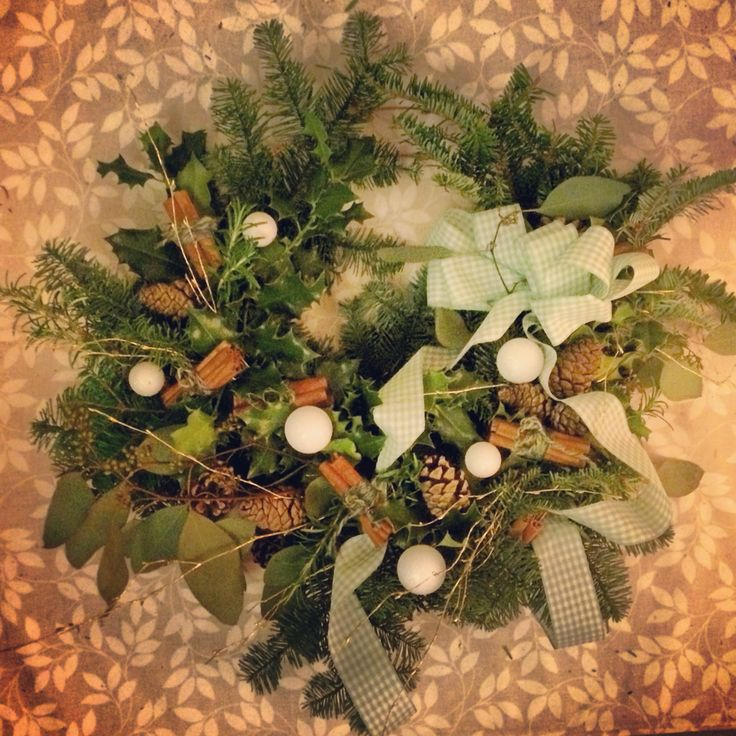 Large spruce, holly and eucalyptus wreath with thyme and cinnamon for added scent. Green gingham cascading bow and sparkly white baubles.