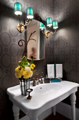 The mixture of dark and light grays and the blue lights on either side of the mirror create a very cold, yet elegant bathroom.  The room is brightened with the yellow flowers as well as the white sink.