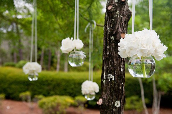 Stunning floral arangements hanging from trees can highlight the ceremony area