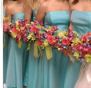The bridesmaids carried smaller versions of the bridal bouquet, tied with bright green satin ribbon. Following her bold color palette, the bride chose strapless aqua bridesmaid dresses that had a layer of tulle peaking out below their tea-length hemlines.