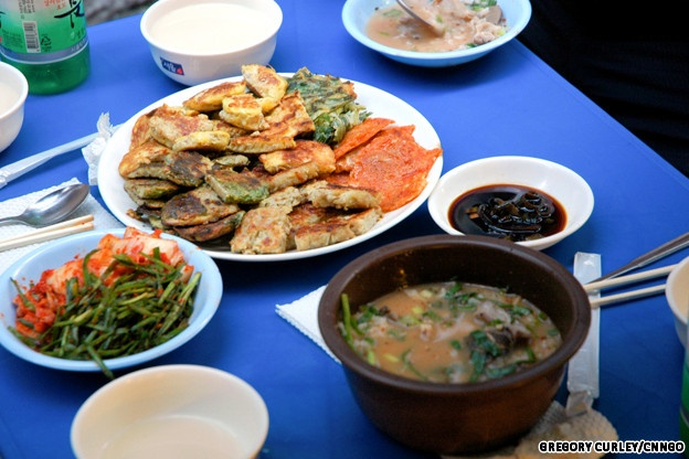 Pajeon (traditional pancake), kimchi and a smaller bowl of noodles ...