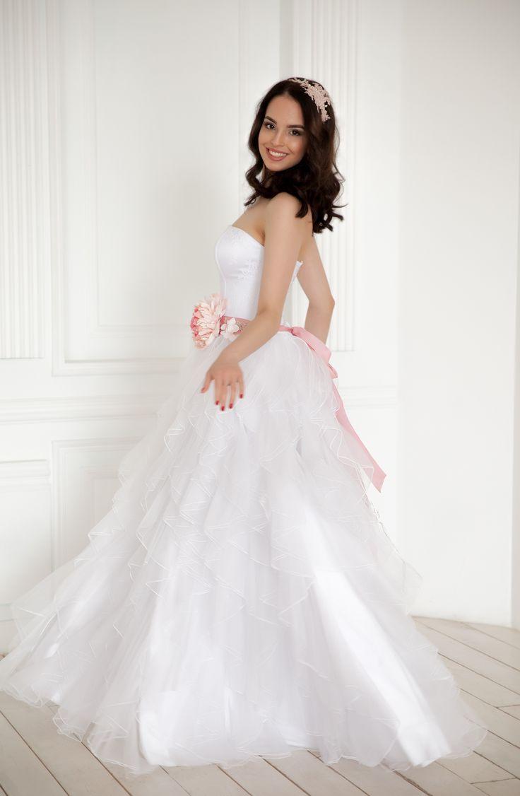 Пышное белое платье с многослойной юбкой и топом с вырезом сердечко. Украшено поясом нежно-розово цвета с красивым нежно-розовым цветком.  Приобрести данное платье можно у нас в разделе катало на нашем сайте: www.fairytaleforyou.com
