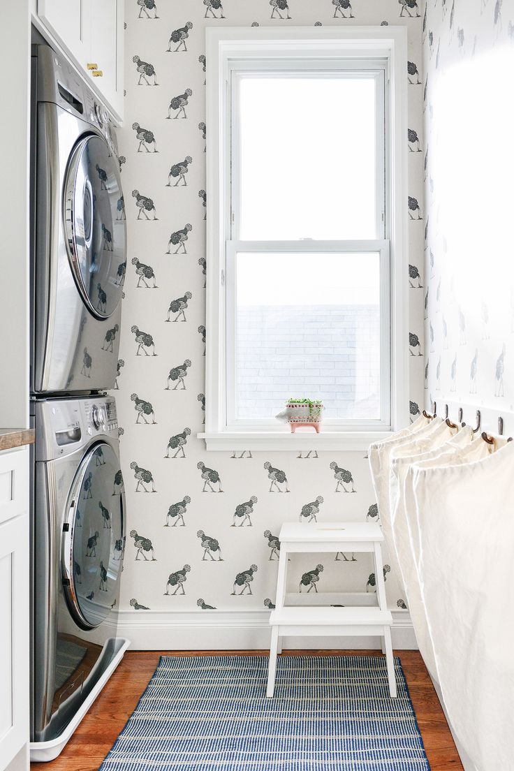 Small laundry room idea with ostrich wallpaper and hamper bags to keep it  organized | via