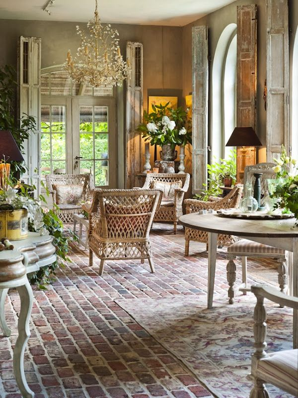 Orangery with brick floor, wicker furniture & weathered shutters - photo by Claude Smekens