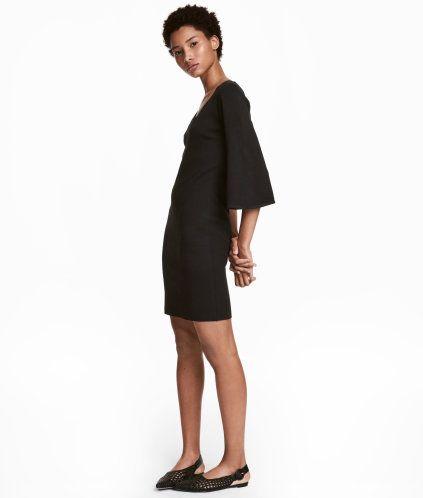 Svart. En figurnära, finstickad klänning i stadig kvalitet med inslag av ull. Klänningen är v-ringad och har vid, trekvartslång ärm.