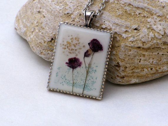 This necklace features a pendant with pressed flower and coloured sand. Flowers are laid in glossy crystal resin on a platinum plated bezel. The background is white resin.