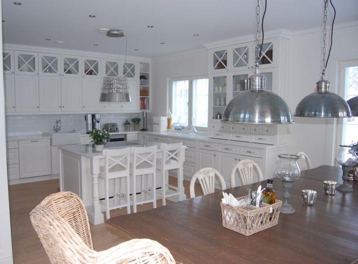 Valkoisessa, maalaisromanttisessa keittiössä valaisimet tuovat ilmettä sisustukseen. Saarekkeen keittiöpuolella on tasoon asennettu induktioliesi. Saarekkeen ruokailutilan puolella taso ulottuu kaapinrungon yli jättäen tilaa kolmelle apukokin tuolille. #puuvaja