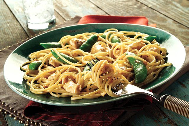 Italian dressing flavors the chicken strips and peanut sauce in this Asian-style pasta meal. Crisp, green sugar snap peas add color and crunch.