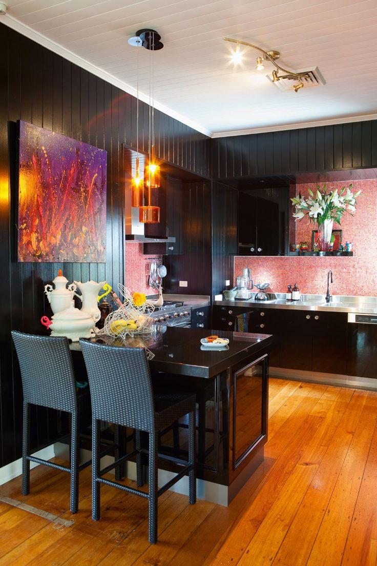 This dark walled kitchen and colourful backsplash make a striking combination