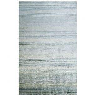 Ultra glamour, chatoyant avec des jeux de lumières et ces fines rayures ondulantes, ce tapis est noué à la main en viscose dans un subtil jeu dégradé de bl
