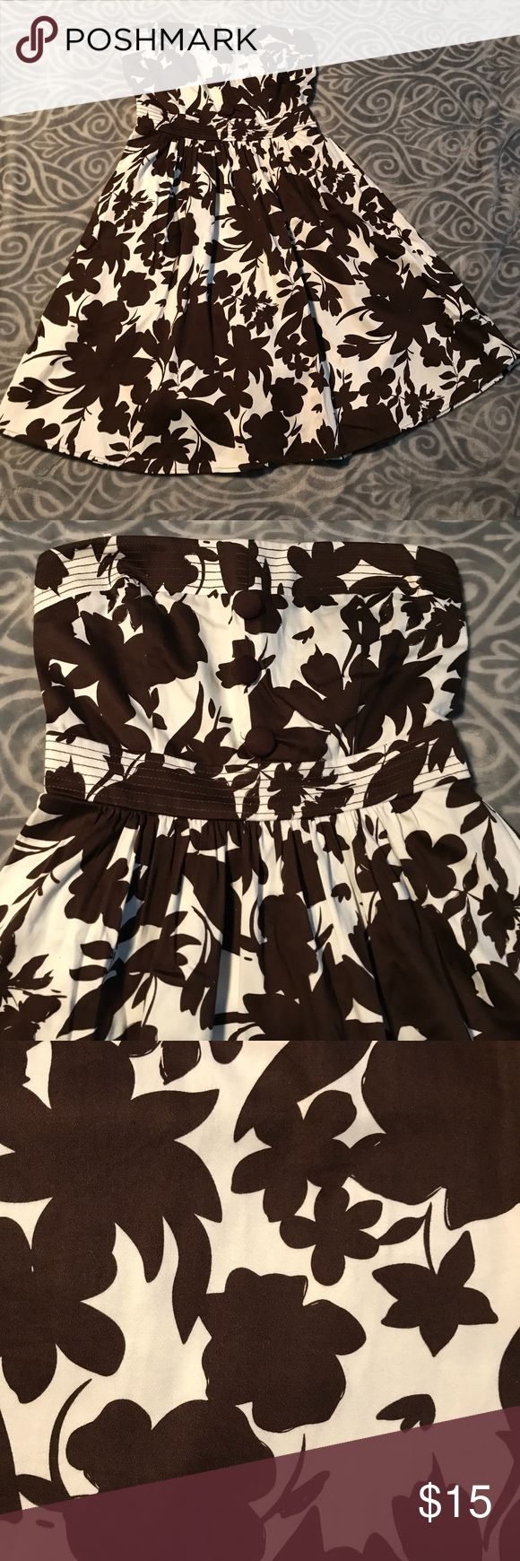 Brown and white floral strapless dress B. Smart brown and white floral strapless dress. Three decorative buttons run down the middle of the chest area. There are two sashes attached to the waist that can tie in the back. Soft, sturdy fabric. Size 4. Transitions well into fall and winter with a cardigan and knee high boots. B.Smart Dresses Strapless