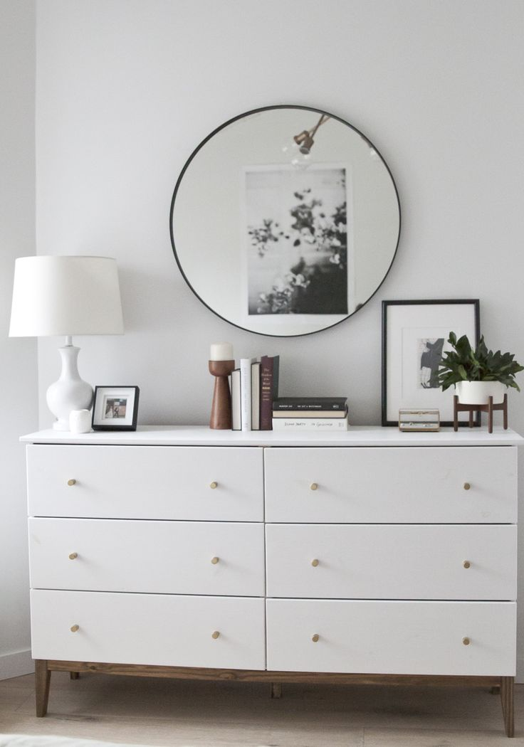 A white, bright, modern dresser with brass knobs and a walnut base