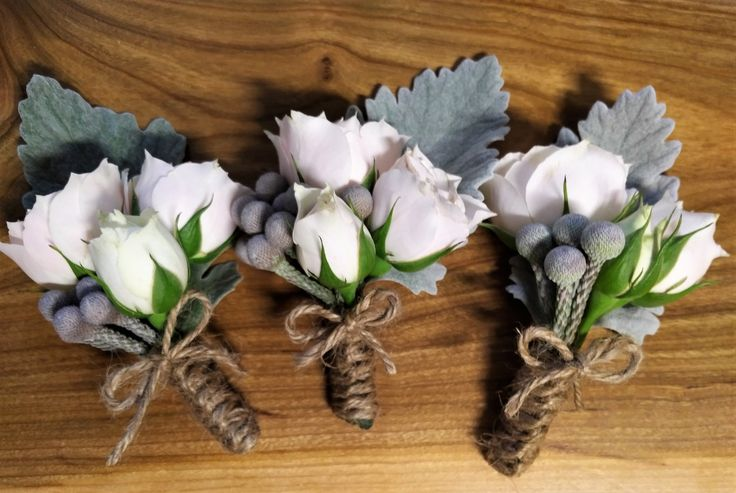 Boutonnieres for the groomsmen.  majolica spray roses, brunia berries, dusty miller, satin ribbon, braiding up the stems.  perfect wedding designs