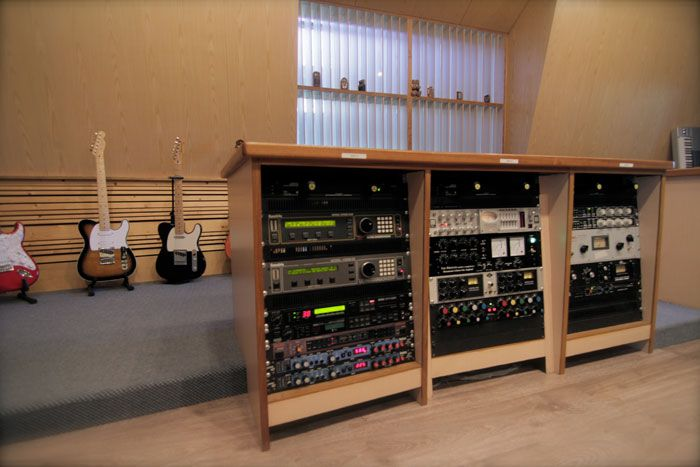 Outboard racks and guitars in the control room at Karma Sound