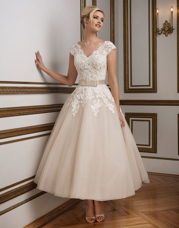 Justin Alexander wedding dresses style 8815 Oyster/Ivory Size 18. A 1950's vintage inspired V-neckline tulle tea length ball gown rich in hue. Silk Dupion band accented with a bow cinches the waistline for a figure flattering look.