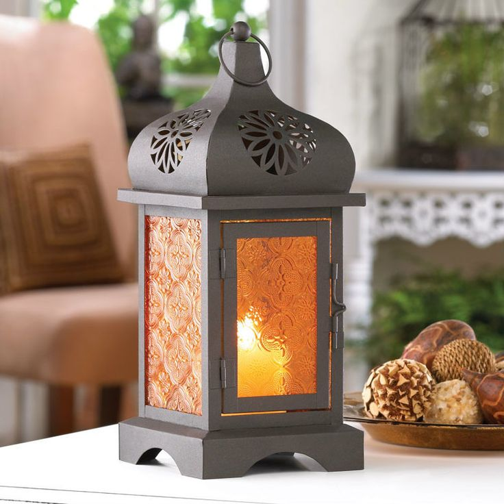 Metal lantern in a gorgeous Moroccan style with amber pressed glass. Looks like a sunset!   Weight: 1.6 pounds 4.75 x 4.75 x 11.75 inches tall Candle not included