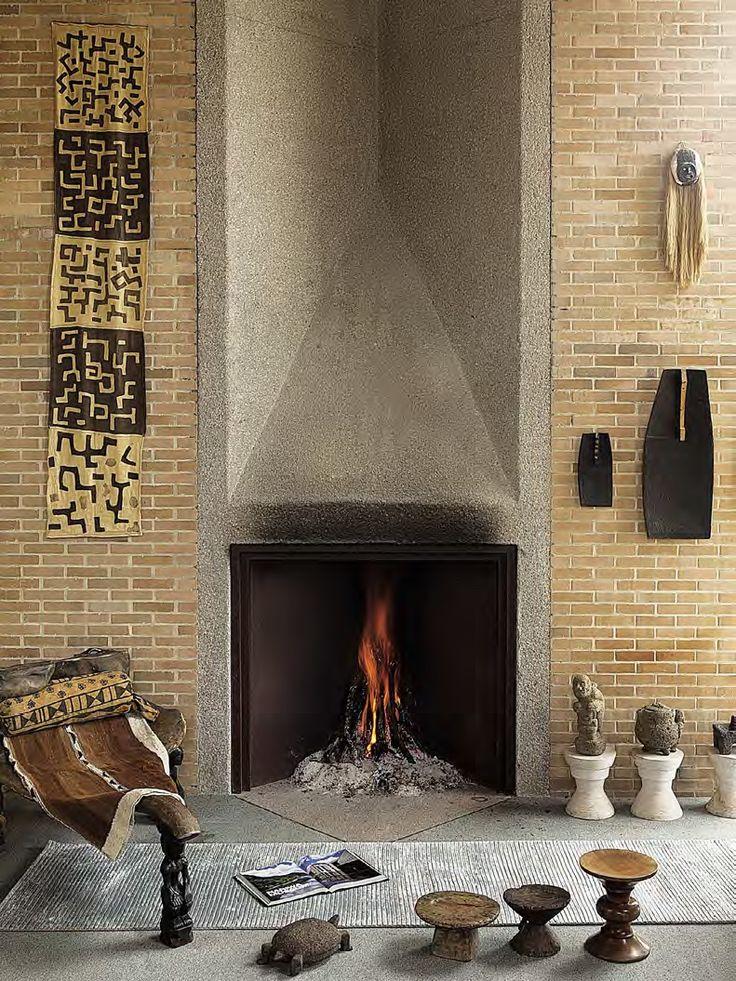 Los materiales naturales de este ambiente acompañan la presencia del fuego a través de una paleta sobria y de diseños nacidos en tiempos inmemoriales. La potente geometría de la chimenea se acompaña de piezas que, sin ostentación, dirigen el recorrido de la mirada. Los textiles de estilo étnico que se repite en las estatuillas de barro a la derecha suavizan la consistencia del ladrillo y del concreto.