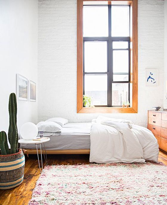 white bedroom with cacti and wood accents