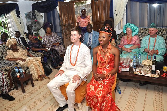 Inter-racial marriage. Nigerian bride wearing a custom-made sleeveless two-piece Edo outfit by Boriah Clothier. Multiple rows of burnt orange traditional beads worn around the circumference of her twisted bun. More wedding pictures and video with explanation of the wedding on the blog.