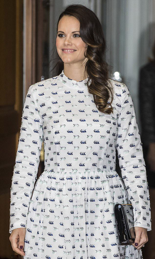 Princess Sofia of Sweden dazzles in a pretty patterned dress with her hair cascading over her shoulder and carried a black patent leather clutch, during an event for their charity foundation at the Royal Palace in Stockholm.