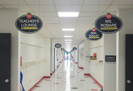 Wow! What an AWESOME transformation!  Your RoomTagz hallway signs look great.  The principal admitted he was reluctant to purchase the double-sided hallway signs at the suggestion of a few teachers who saw them on Pintetest, but enthusiastically relieved he did because of the difference they make.  Each sign is approximately $50 and includes sign, all the vinyl lettering needed to personalize, and hanging hardware.  The lettering is easily removable & replacable when a change in staff occurs!