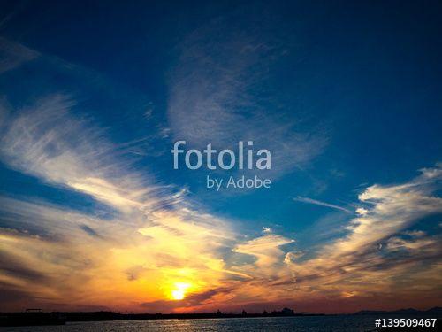 """ロイヤリティーフリーの写真 """"広がる空と街に沈む太陽を対岸から眺めた夕焼け空。まだ一日が整理しきっていないけれども、早々と太陽は沈んでしまう様子。"""" は mitsuruy が作成し、Fotolia.com から格安でダウンロードできます。弊社のお手頃な価格の画像コレクションを閲覧して、マーケティングプロジェクトなどにぴったりのストックフォトを見つけて下さい!"""
