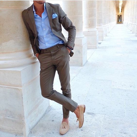 Sharp looking neutral suit with a blue shirt underneath and neutral tassel loafers.