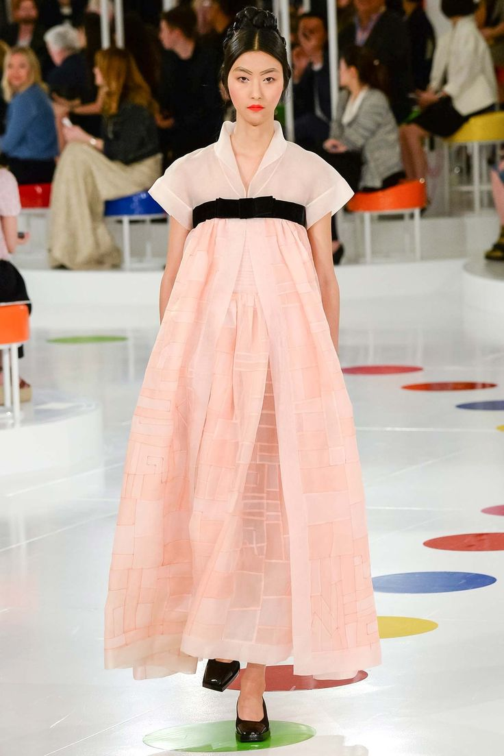 """Chanel Resort 2016 Fashion Show """"Karl's in Korea for cruise. An extravagant, exuberant event cementing the relationship between Chanel and its Seoul sisters culminated with a graceful cross-cultural compliment: a fragile semi-sheer two-tone pink linen hanbok dress with a wide black ribbon tied in a bow. """"You know, it is made in a special linen patchwork technique, which was done here because no one else can make it,"""" remarked Lagerfeld..."""