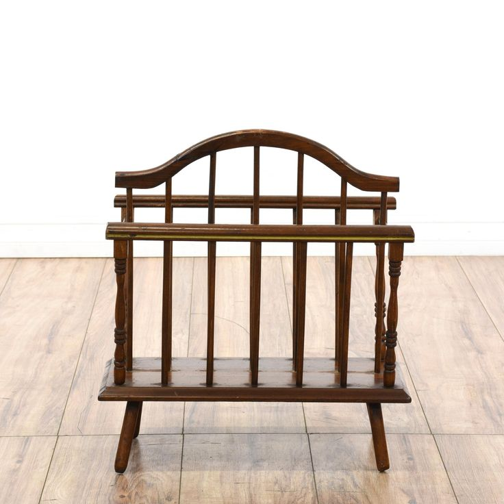 This magazine rack is featured in a solid wood with a mahogany stain. This traditional style magazine stand has 2 sections with a middle divider, a handle for easy mobility, and carved spindle details. Perfect for organizing magazines! #americantraditional #storage #magazinerack #sandiegovintage #vintagefurniture