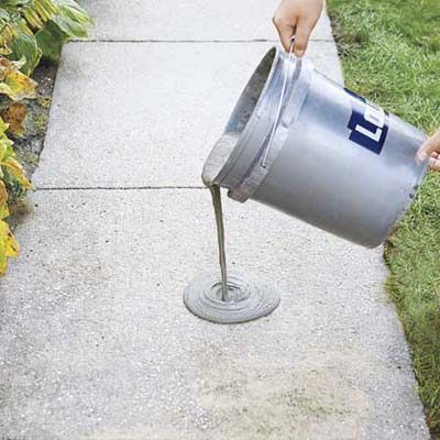 pouring the resurfacer onto the concrete walkway with a 5-gallon bucket