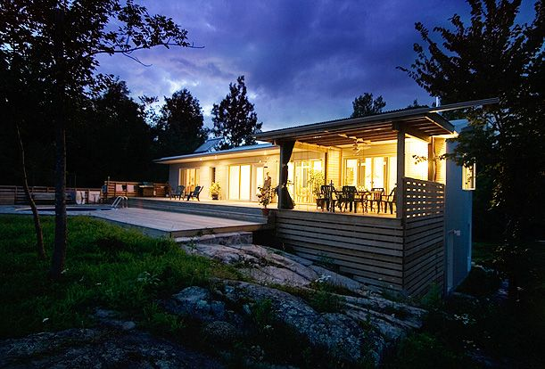 Gananoque Lake Road House - The rock outrcropping rises out from under the screened porch.  The screens slide on tracks enabling them to be opened or closed at a moment's notice.