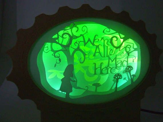 Illuminated in green and blue LED , this is the second Alice in Wonderland lamp in our Storybook lamps series.  Like the other lamps in this series, the scene of this wonderful tale , is cut out of Vinyl. The scene is illuminated by green and blue LED that also projects a magical light on the wall behind the lamp.  Height : 18 cm Width : 25 cm  Material frame : Oak Filament Material picture : Vinyl