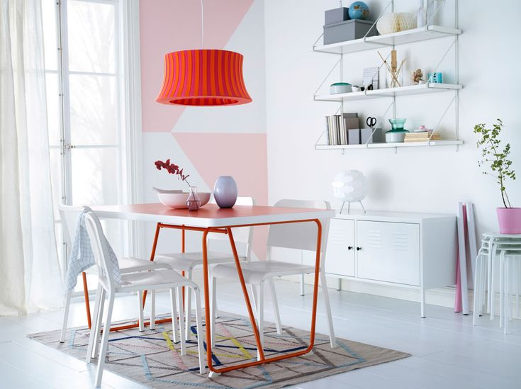 A dining room with a orange dining table and white chairs. Combined with shelves and a steel cabinet, all in white.