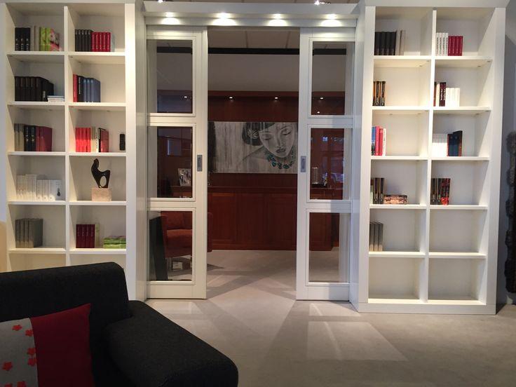 Kamer en suite deuren, gecombineerd met boekenkasten. Op de achtergrond een bibliotheek in Kersenfineer uitgevoerd.