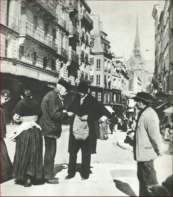 """Un mégotier vend sa marchandise, place Maubert, en 1895. La """"marchandise"""" était soit du tabac gros, résidu de cigares et de fonds de pipes, soit du tabac fin, qu'ils fabriquaient avec des bouts de cigarettes..."""
