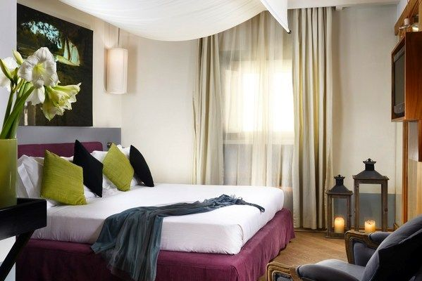 Mario de' Fiori 37 - Double Deluxe: This cozy sanctuary, styled with warm wood accents and original artwork, features a king-size bed with Frette sheets, plush pillows, and a romantic canopy.