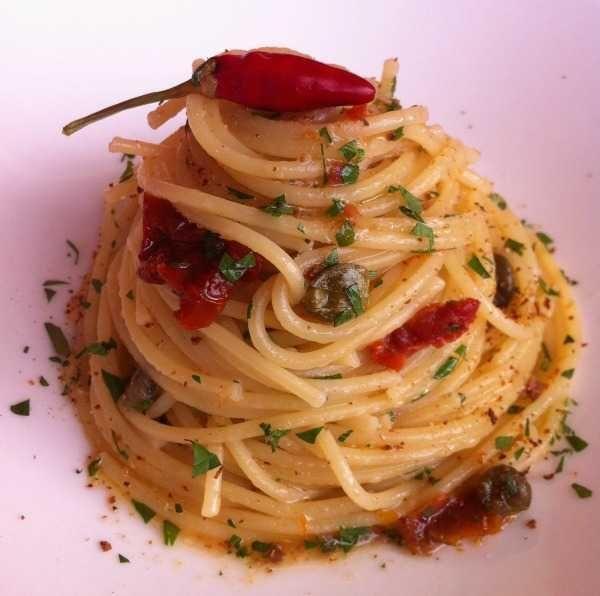 Spaghetti con colatura di alici e pomodori secchi.   Ingredienti: 160 gr di spaghetti; 3 pomodori secchi sott'olio; 2 filetti di alici di Cetara sott'olio; 1 cucchiaio di capperi; 2 cucchiai di colatura di alici; 1 spicchio di aglio; un pizzico di peperoncino; prezzemolo fresco tritato; 4 cucchiai di olio extravergine di oliva; pangrattato tostato